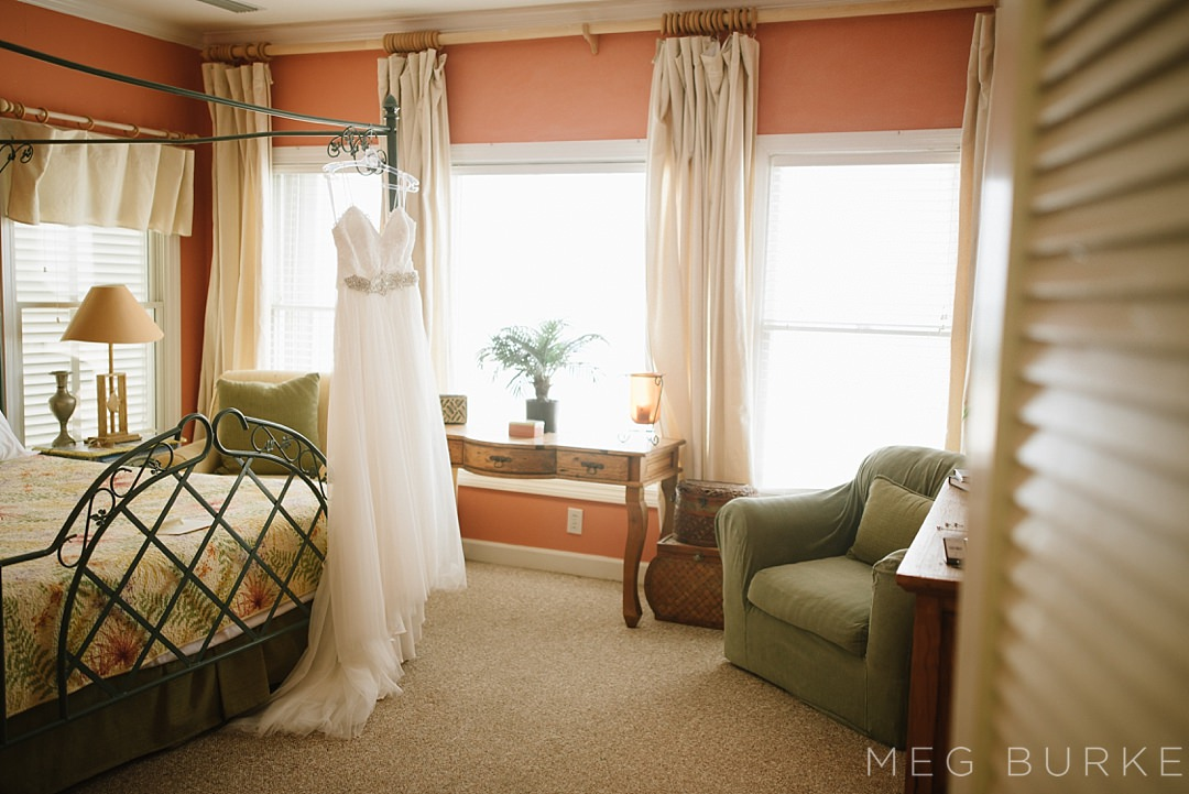 wedding dress hanging on bed post