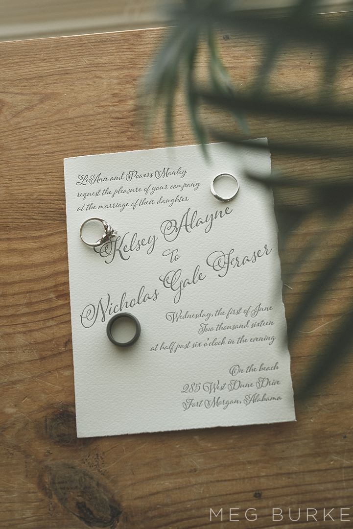 wedding bands on invitation suite with palms