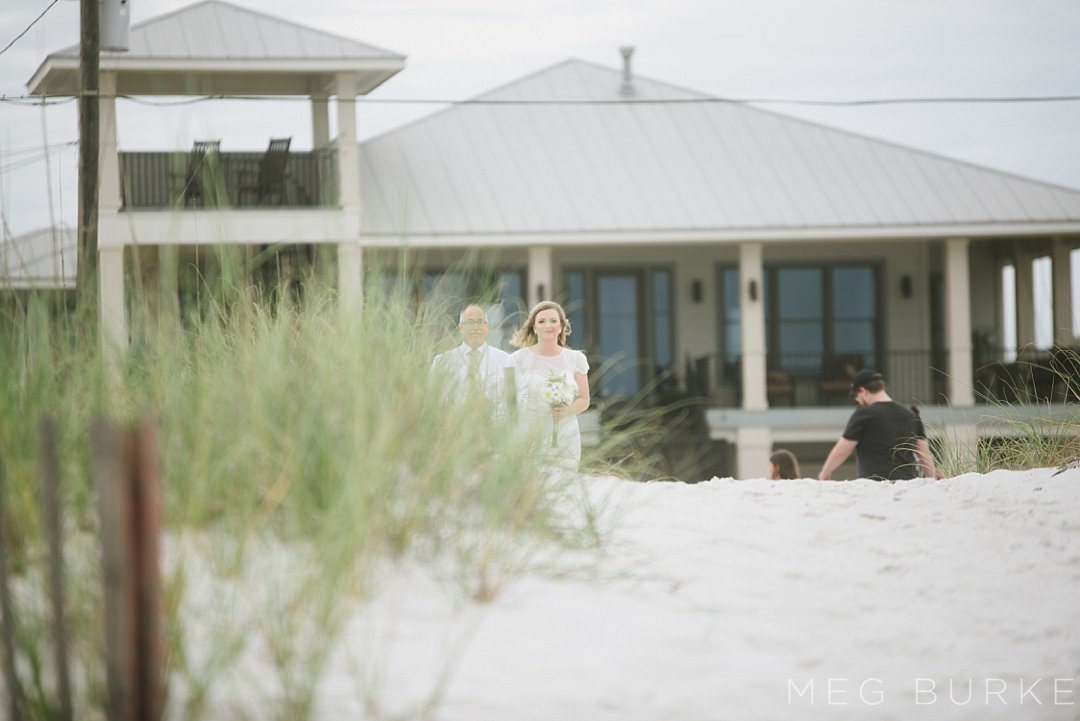 bride entering beach ceremony with father
