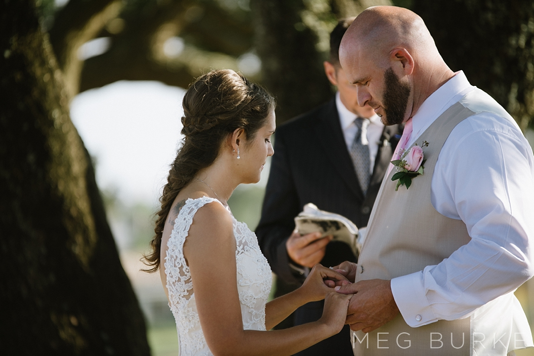 Outdoor ceremony exchanging vows by a tree