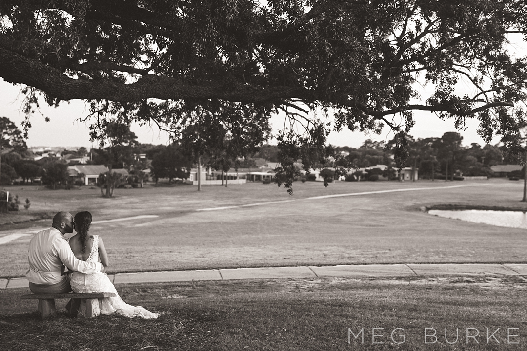 Bride and groom under oak tree on golf course