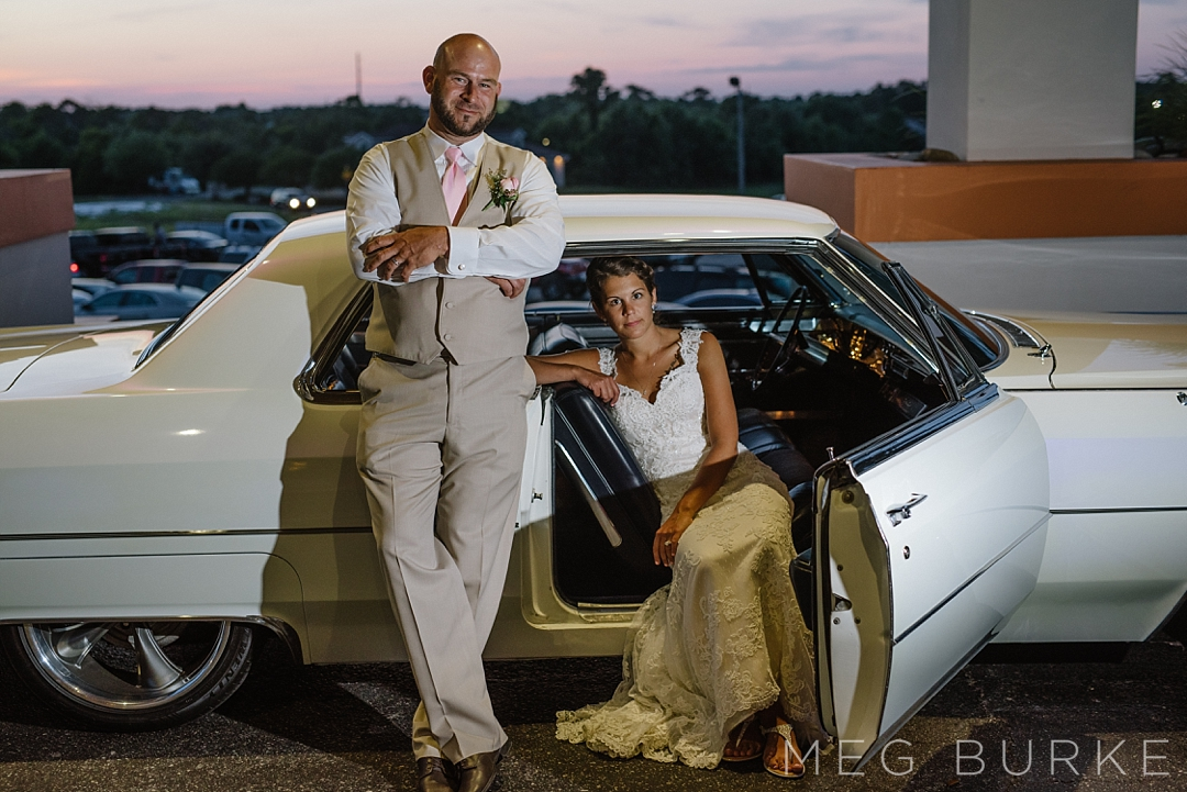 Bride and groom in a white cadillac